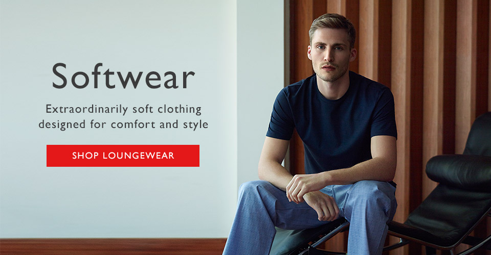 Man wearing luxury loungewear sitting down. Navy lounge t-shirt and prince of wales checked trouser