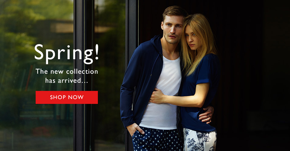 Man and woman wearing luxury loungewear in front of glass patio door